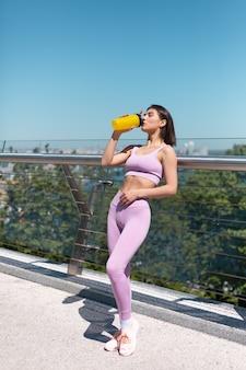 Jeune femme en vêtements de sport de montage sur le pont au matin chaud et ensoleillé avec une bouteille de shaker d'eau assoiffé après l'entraînement de boire fatigué