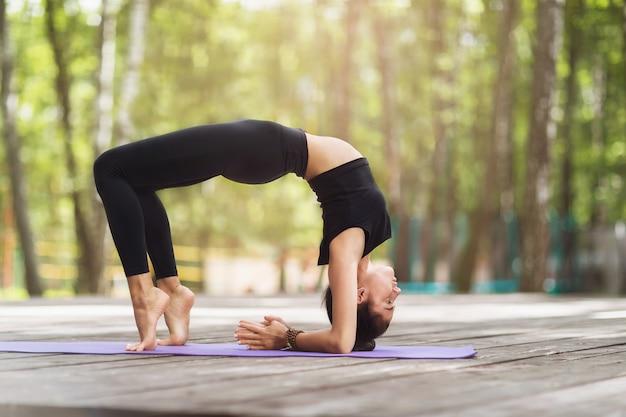 Une jeune femme en vêtements de sport pratiquant le yoga effectue un exercice de pont fermé sur un tapis dans le parc
