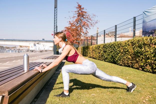 Jeune femme en vêtements de sport qui s'étend de la jambe en plein air