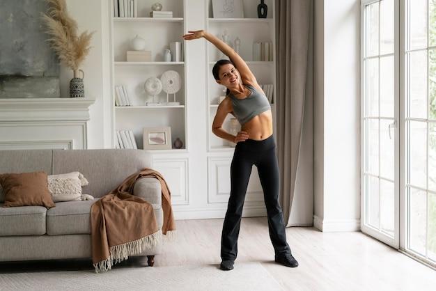 Jeune femme en vêtements de sport s'exerçant à la maison