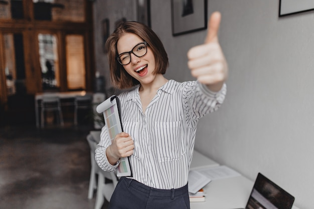 Jeune femme en vêtements de style bureau et lunettes tient la tablette avec des documents, des clins d'œil et montre le pouce vers le haut.