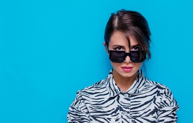 Jeune femme en vêtements de zèbre et lunettes de soleil sur fond bleu