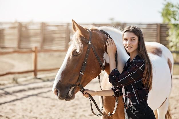 Jeune femme vétérinaire calmant un cheval malade regardant la caméra en souriant.
