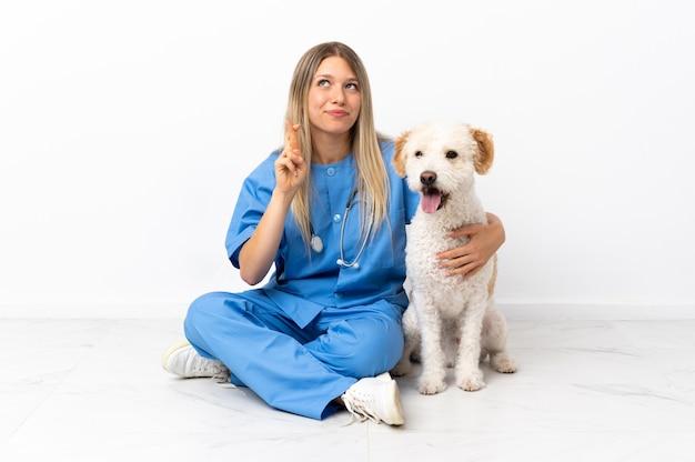 Jeune femme vétérinaire avec chien assis sur le sol avec les doigts qui se croisent et souhaitant le meilleur