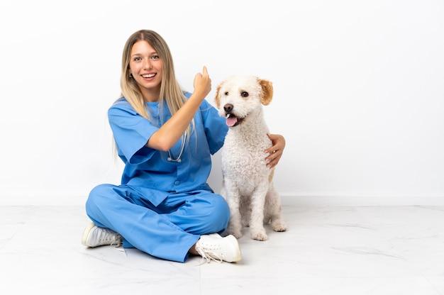 Jeune femme vétérinaire avec chien assis sur le sol pointant vers l'arrière