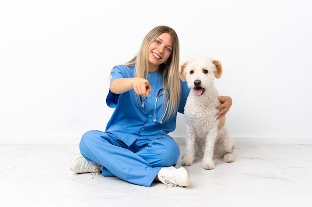 Jeune femme vétérinaire avec chien assis sur le sol pointant vers l'avant avec une expression heureuse