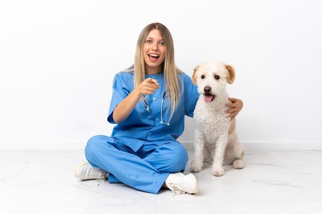 Jeune femme vétérinaire avec chien assis sur le sol surpris et pointant vers l'avant