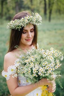 Une jeune femme vêtue d'une belle robe tendre et une couronne tient un bouquet de camomille dans ses mains