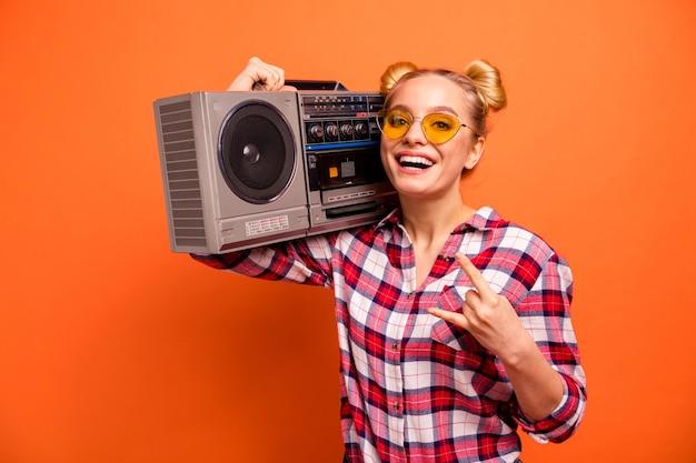Jeune femme vêtue d'une chemise à carreaux à carreaux isolée sur orange avec boombox