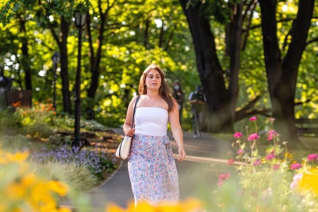 Une jeune femme vêtue d'un haut léger et d'une jupe panachée se promène dans le parc de la ville, fleurs défocalisés au premier plan