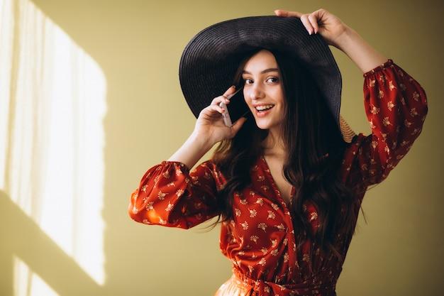 Jeune femme vêtue d'une jolie robe avec téléphone et shopping en ligne