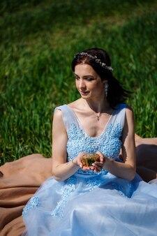 Une jeune femme vêtue d'une longue robe bleue est assise contre un champ vert avec un cercueil dans les mains. mode portrait d'une belle fille avec un sourire sur son visage. boîte à bagues de fiançailles
