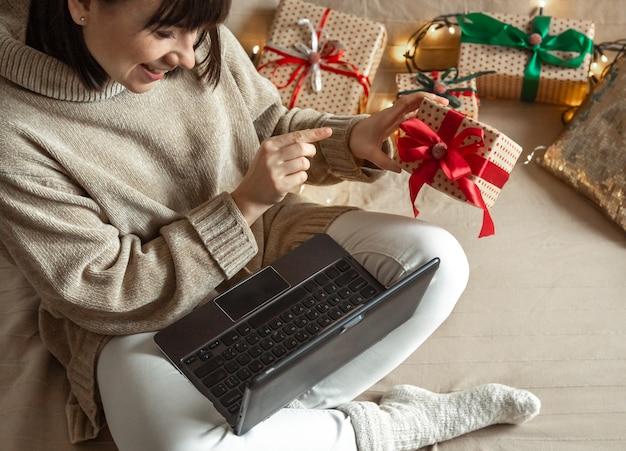 Une jeune femme vêtue d'un pull douillet achète des cadeaux de noël sur internet. concept de choix de cadeaux en ligne et à distance.