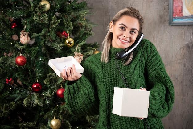 Jeune femme vêtue d'un pull vert à l'aide de téléphone vintage près de l'arbre de noël