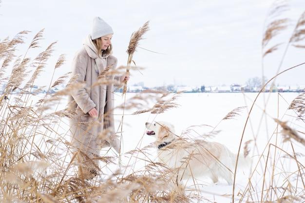 Une jeune femme vêtue d'une robe beige de couleurs neutres recueille l'herbe de la pampa
