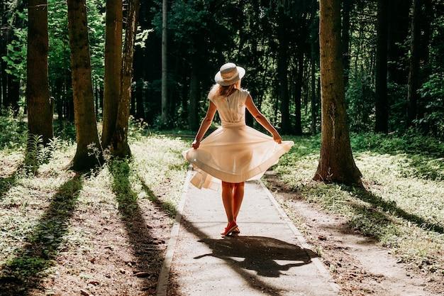 Une jeune femme vêtue d'une robe blanche et d'un chapeau de paille se promène dans les bois