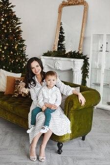 Jeune femme vêtue d'une robe est assise avec un petit garçon sur le canapé près de l'arbre de noël dans le salon