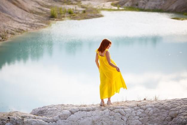 Jeune femme vêtue d'une robe jaune près du lac avec de l'eau azur et des arbres verts.