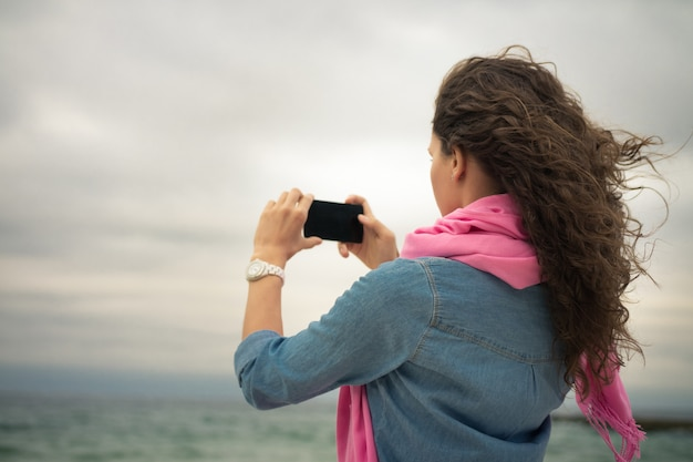 Jeune femme vêtue d'une robe en jean avec une écharpe rose prend une photo de la mer