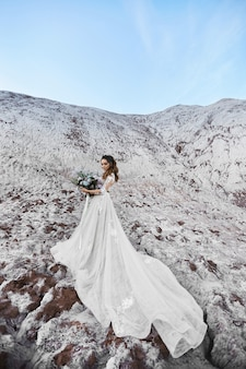 Jeune femme vêtue d'une robe de mariée gardant un bouquet de mariée et posant sur une montagne par une journée d'été ensoleillée.