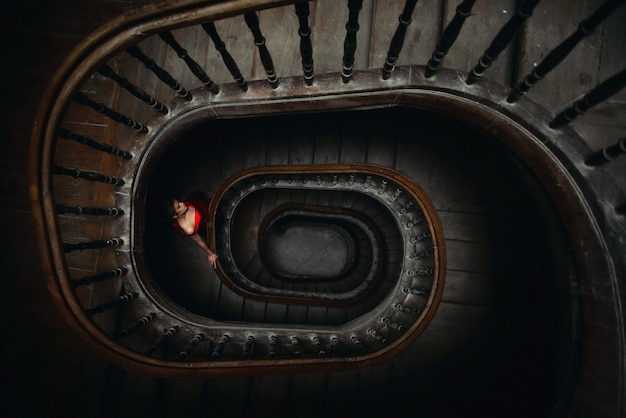 Jeune femme vêtue d'une robe rouge descend les escaliers tourbillonnants en bois.