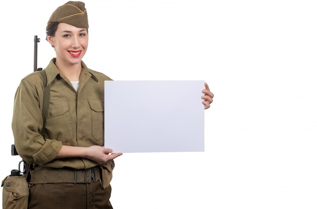 Une jeune femme vêtue de la seconde guerre mondiale nous militaire en uniforme montrant une enseigne vierge vide avec un fond