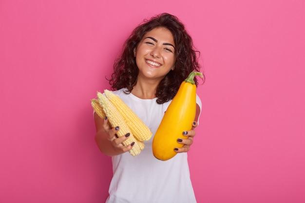 Jeune femme vêtue d'un t-shirt décontracté blanc montrant des courgettes et des épis de maïs à la caméra, a une expression faciale heureuse, posant avec un sourire à pleines dents. régime alimentaire cru et concept de saine alimentation.
