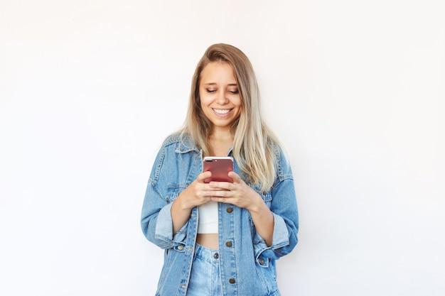 Une jeune femme vêtue d'une veste en jean et d'un jean sourit et tient un téléphone portable en regardant l'écran
