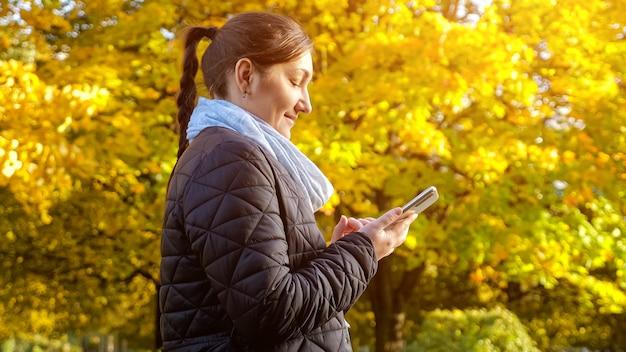 Une jeune femme vêtue d'une veste noire et d'une écharpe grise tape un message au téléphone
