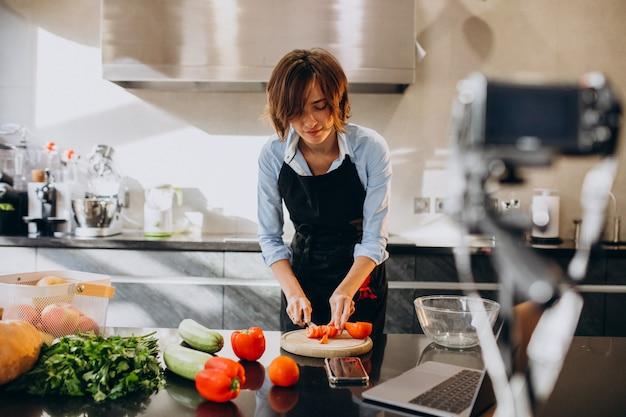 Jeune femme vidéoblogger en train de cuisiner à la cuisine et de filmer