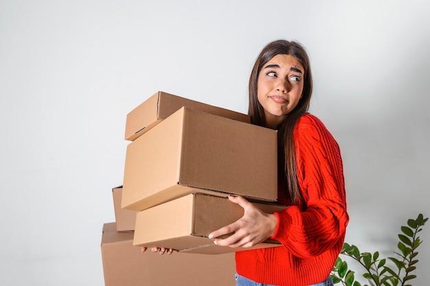 Une jeune femme vient d'emménager dans un nouvel appartement vide, déballage et nettoyage - déménagement. jeune fille transportant des boîtes en carton à la nouvelle maison.