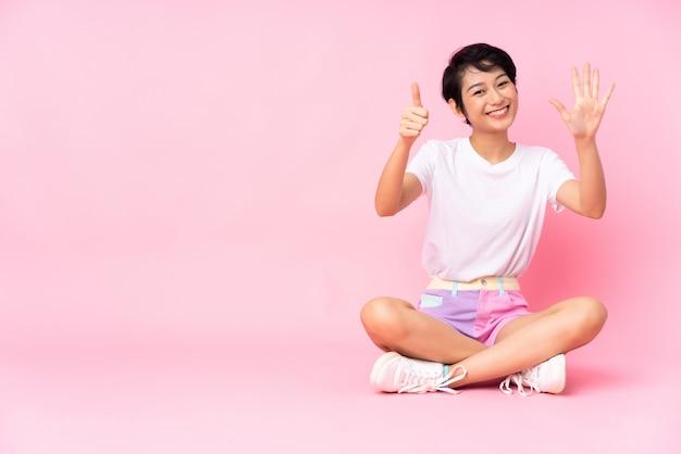 Jeune femme vietnamienne aux cheveux courts assis sur le sol sur le mur rose comptant six avec les doigts