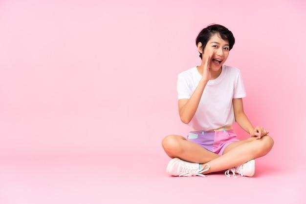 Jeune femme vietnamienne aux cheveux courts assis sur le sol sur le mur rose criant avec la bouche grande ouverte