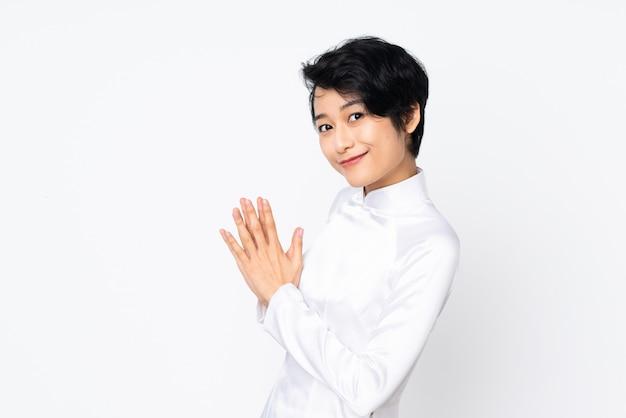 Jeune femme vietnamienne aux cheveux courts portant une robe traditionnelle sur un mur blanc complotant quelque chose