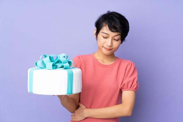 Jeune femme vietnamienne aux cheveux courts tenant un gros gâteau sur le mur violet avec une expression triste