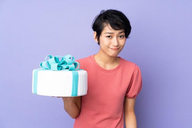 Jeune femme vietnamienne aux cheveux courts tenant un gros gâteau sur un mur violet isolé avec une expression triste