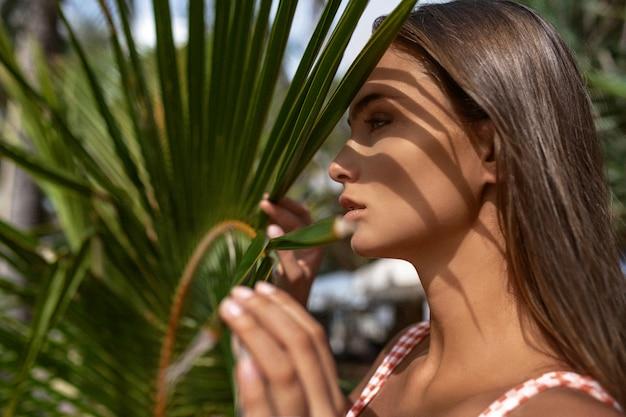 Jeune femme visage agrandi, profil. modèle de spa attrayant avec une peau saine, feuilles de palmier vert -