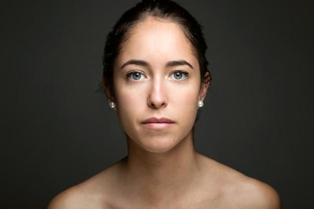 La jeune femme avec un visage de beauté. isolé sur blanc.