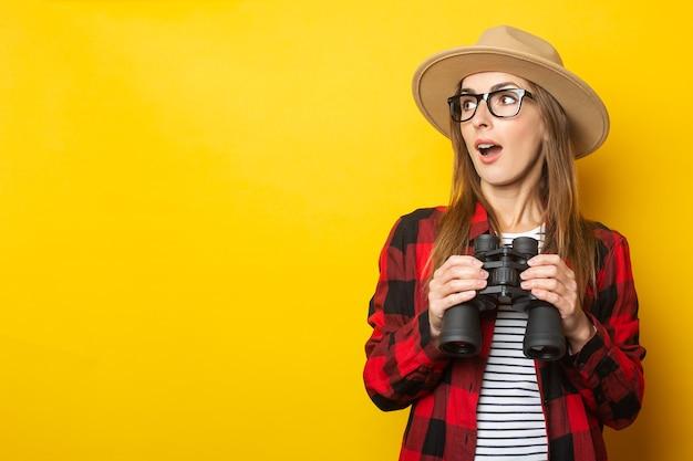 Jeune femme avec un visage surpris dans un chapeau et une chemise à carreaux tenant des jumelles dans ses mains sur un fond jaune.