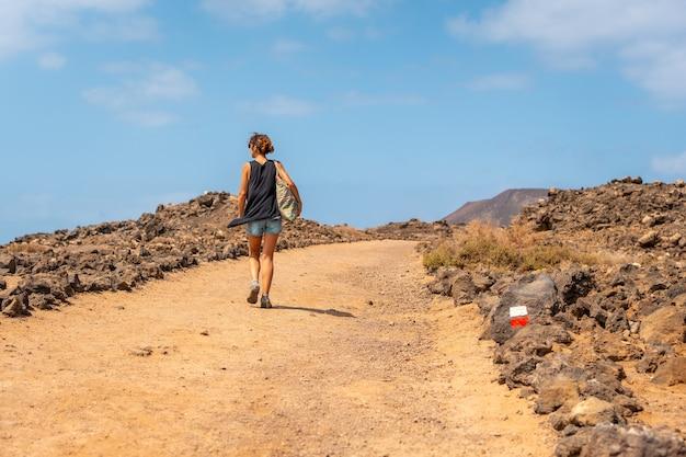 Une jeune femme visitant l'isla de lobos, le long de la côte nord de l'île de fuerteventura, îles canaries. espagne