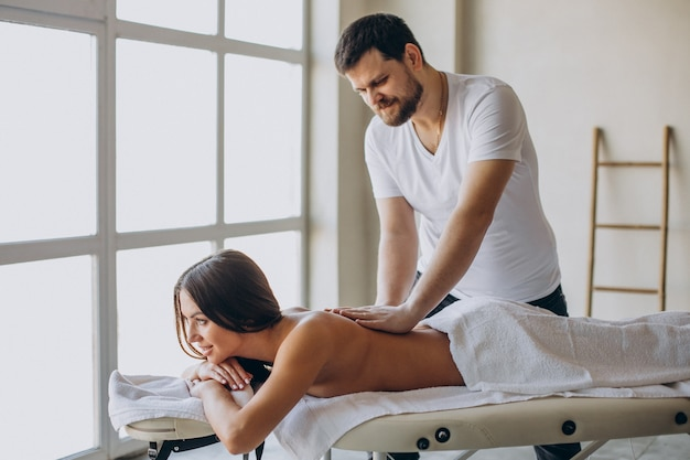 Jeune femme visitant le masseur au centre de spa