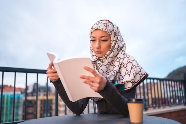 Jeune femme avec voile blanc à l'ordinateur sur la terrasse d'un café, lisant un beau livre