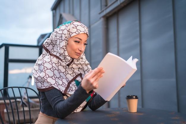 Jeune femme avec voile blanc à l'ordinateur sur la terrasse d'un café, s'amusant beaucoup à lire un beau livre
