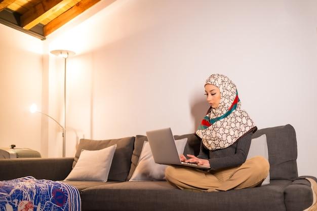Jeune femme avec un voile blanc à son ordinateur personnel sur le canapé de son salon, faisant un travail
