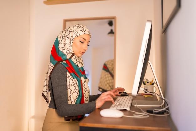Jeune femme voilée à l'ordinateur à la maison, travaillant à domicile