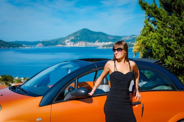 Jeune femme avec voiture au bord de la mer