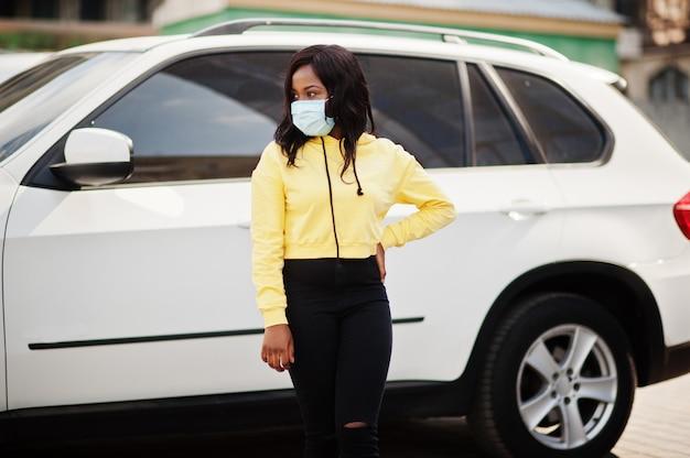 Jeune femme volontaire afro-américaine portant un masque facial à l'extérieur contre une voiture suv. quarantaine de coronavirus et pandémie mondiale.