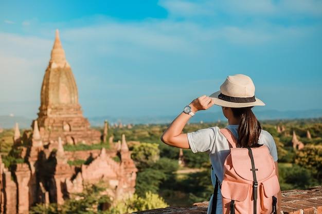 Jeune femme voyageant backpacker avec chapeau, voyageur asiatique debout sur la pagode
