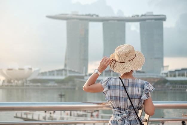Jeune femme voyageant avec un chapeau le matin, visite d'un voyageur asiatique heureux dans le centre-ville de singapour. point de repère et populaire pour les attractions touristiques. concept de voyage en asie