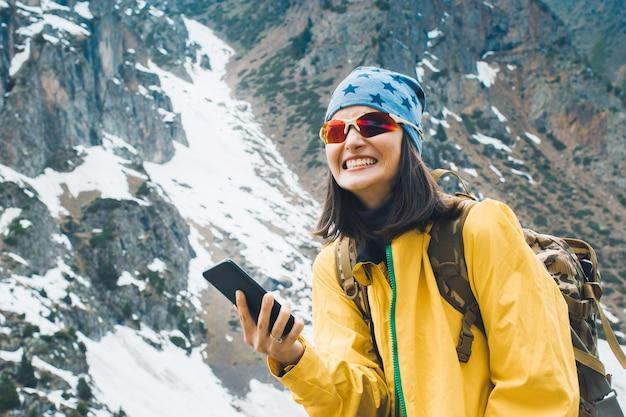 Jeune femme voyageant émotion parlant sur smartphone dans les montagnes rocheuses